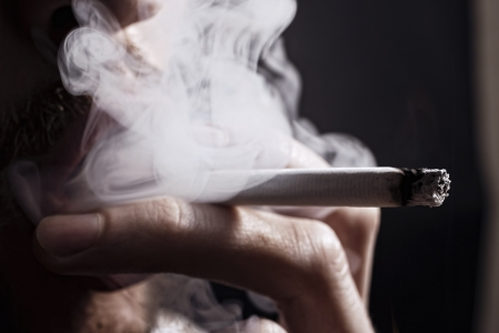cigarette smoke: smoking cigarette in the hand of young man close up