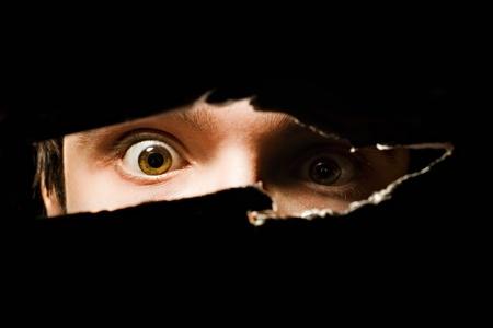 Enge ogen van een mens spionage door een gat in de muur Stockfoto
