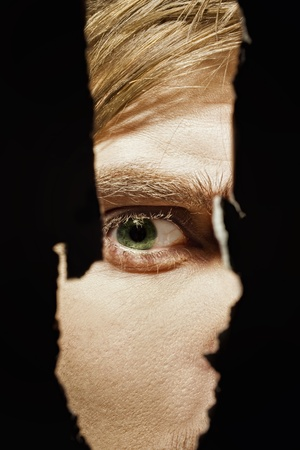 Scary eyes of a man spying through a hole in the wall Stock Photo - 10200651