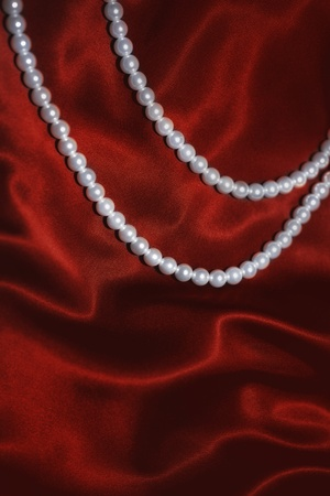 white pearl necklace on a red silk close up photo