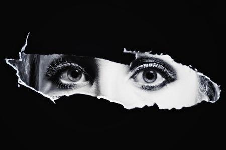 Womens bl eyes spying through a hole photo