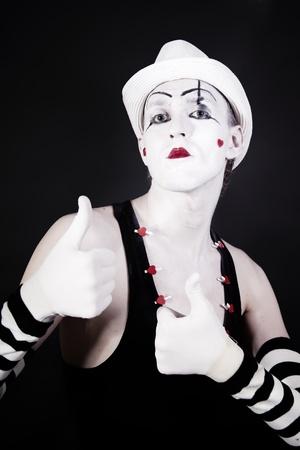m�mica: actor de teatro en maquillaje y un sombrero blanco sobre fondo negro