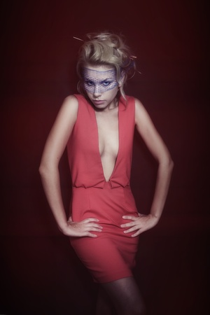 Young beautiful blonde woman in a red dress and veil on dark background photo