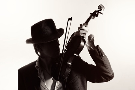 young violinist playing the violin in hat and jacket  on a light background photo