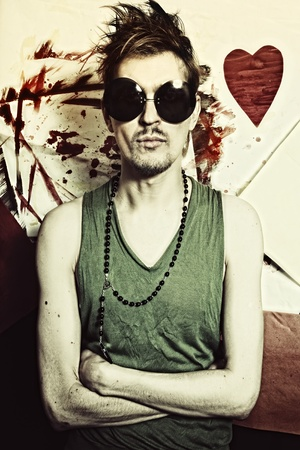 Portrait of young punk in round sunglasses closeup