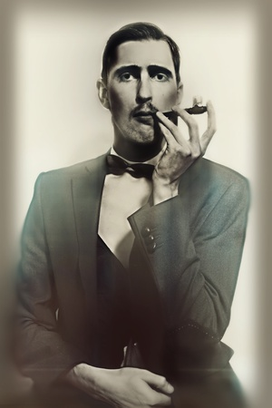 wealthy: retro portrait of an adult man smoking a pipe closeup Stock Photo