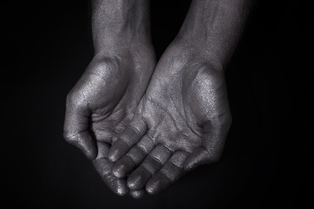 Two hands folded a handful on a black background