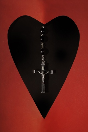 Catholic rosary with a crucifix in a hole shape of heart photo