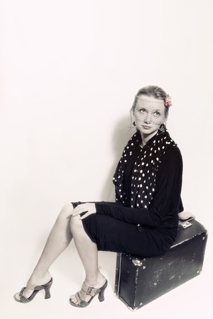 Young beautiful woman in retro style sitting on an old suitcase photo