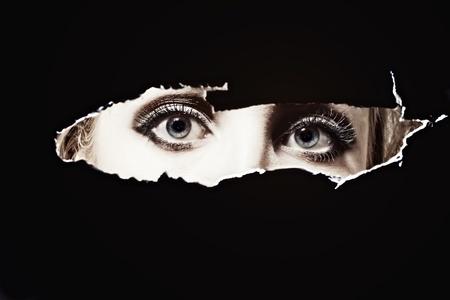 Blauwe ogen van vrouwen spioneren door een gat