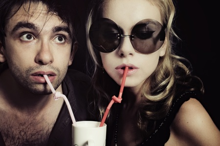 Young man and woman drinking through a tube photo