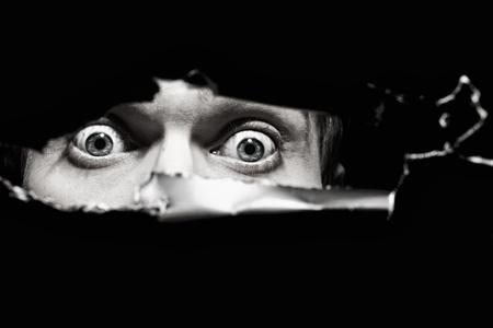 Scary ogen van een man spionage door een gat in de muur close up