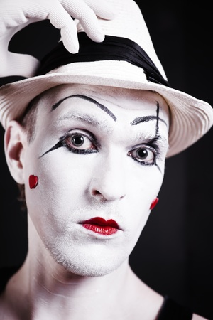 Studio portrait of serious theatrical clown in white hat with red hearts on her face isolated on black background photo