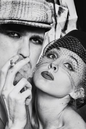 hombre fumando: Estudio de retrato de los hombres y mujeres jóvenes en estilo retro