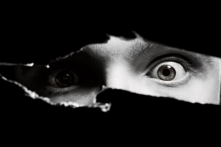 Eng ogen van een mens spionage door een gat in de wand