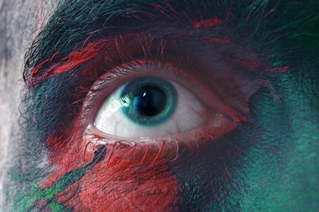 Male blue eyes bright with war paint macro photo