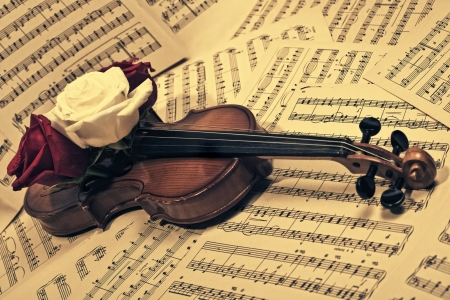 red sheet: old violin with musical notes and roses closeup  Stock Photo