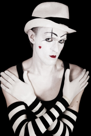 Studio portrait of mime in white hat and striped gloves  isolated on black background photo