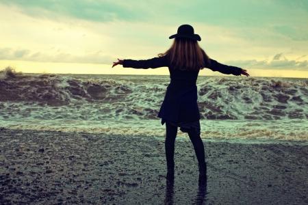back of woman: mujer joven con un abrigo negro y sombrero en la playa