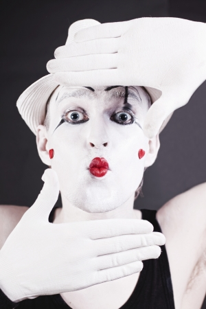 Portrait of a funny mime in white hat on a black background photo