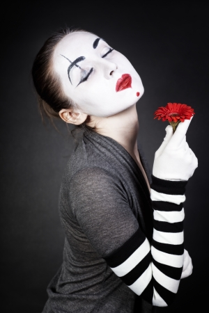 Dreaming woman mime with red flower on black background photo