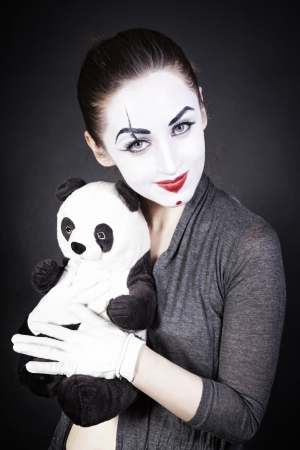 A woman mime with a toy panda on a black background photo