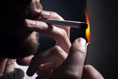 Mens hand lights a cigarette with a match closeup photo