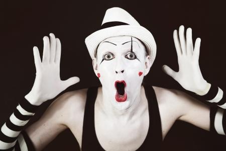 Ape Mime in gestreiften Handschuhen und weißen Hut auf schwarzem Hintergrund Standard-Bild - 14619500