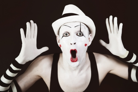 Ape mime in striped gloves and white hat on black background photo