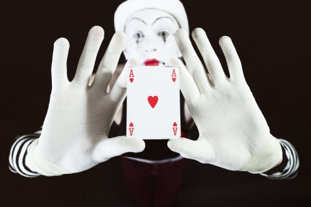 Funny mime holding a ace of hearts on black background close up photo