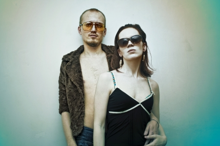 Young man and woman in sunglasses on white background photo
