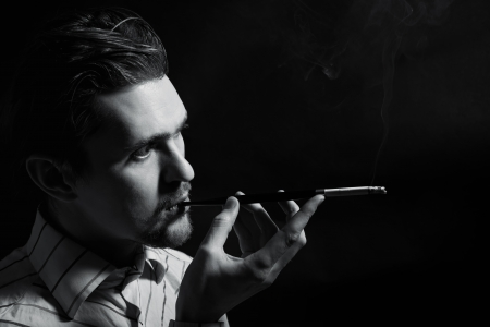 Studio portrait of a young man smoking a cigarette on a black background photo