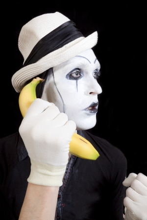mime in white hat holding a banana in his hand close up photo