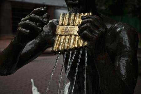 zampona: Estatua de bronce con flauta de pan en sus manos