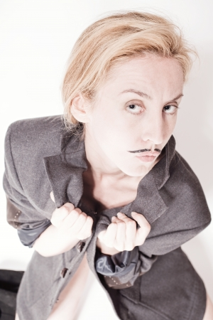 young woman with painted mustache wearing jacket sitting on the floor photo