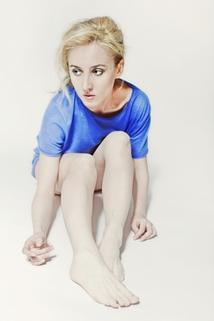 Fair-haired beautiful woman in blue shirt sitting on floor close up Stock Photo - 14718514