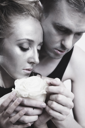 A young couple in love with a white rose and silver make-up photo