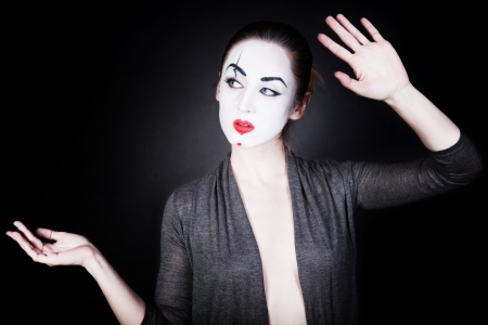 A woman in a theatrical mime make-up dancing on a black background photo
