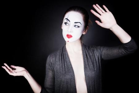 pantomima: Una mujer en una m�mica teatral maquillaje bailando sobre un fondo negro Foto de archivo