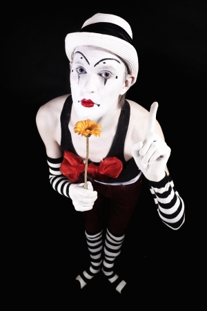 Mime in a white hat, holding a yellow flower on a black background Stock Photo