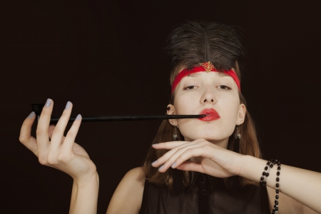 Portrait of a young woman with opium pipe on a black background. retro style photo