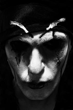 színházi színész sötét smink az arcán közelről