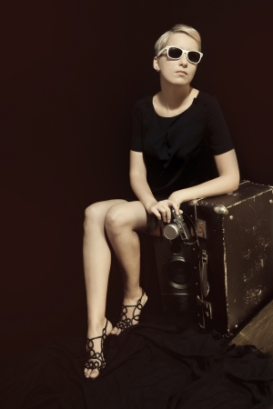young beautiful stylish woman in sunglasses with suitcase and camera photo