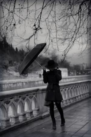 lluvia paraguas: Mujer joven en capa con el paraguas