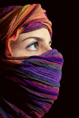 Portrait of beautiful green-eyed woman in hijab on black background