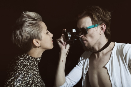Man photographing a young woman in the studio on a black background photo