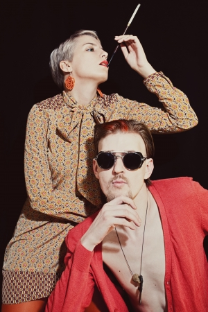 Young stylish couple in sunglasses on black background photo