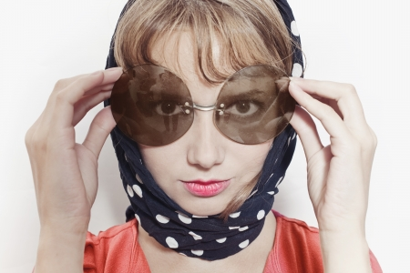 Portrait of a young woman wearing sunglasses and headscarf on a white background photo