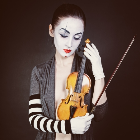 Sad mime with violin on a black background photo