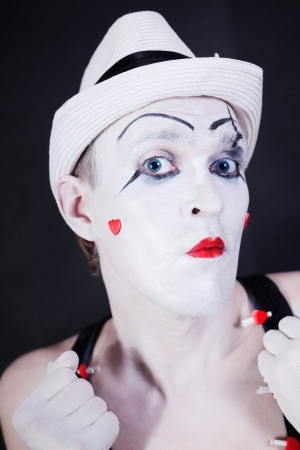 theatrical clown in white hat with red hearts on her face isolated on black background photo